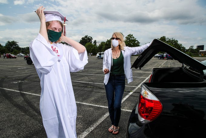 "Teri McGeeney helps daughter and Manual High senior Annie Vinson get ready for the 2020 graduation parade while the two wore masks that many wore due to the coronavirus outbreak. ""I wish my graduation had a parade,"" McGeeney said.  May 24, 2020"