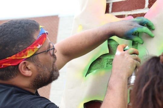 Rafael Serrano sprays temporary chalk onto a mural Saturday at OhioHealth Mansfield Hospital.