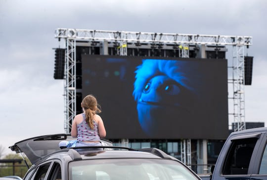 """Audriana Coleman, 8, watches """"Abominable"""" on the top of a car at the Milky Way Drive-In in Franklin. In response to the coronavirus pandemic, the drive-in opened on Memorial Day weekend with some guidelines for social distancing. The drive-in is expected to remain open into the fall."""