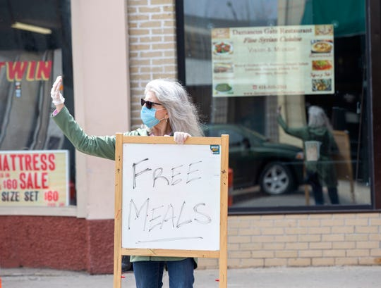 Rev. Karen Hagen, pastor of Tippecanoe Presbyterian Church, shows a free meals sign to cars driving by Damascus Gate.