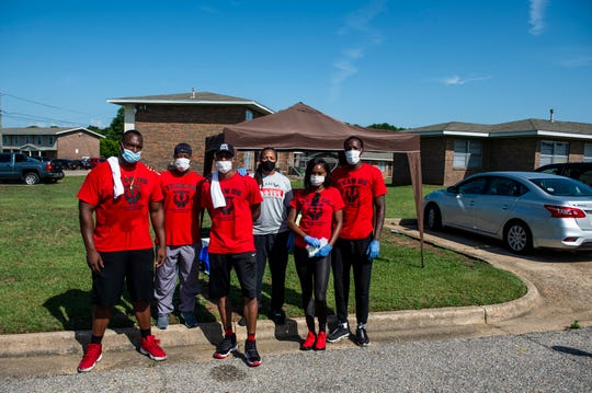 Members of Team US hand out gloves and masks in Gibbs Village in Montgomery, Ala., on Saturday, May 23, 2020.