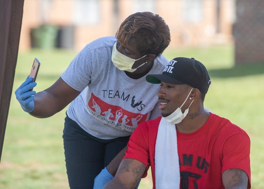 State Rep. TaShina Morris joins members of Team US as they hand out gloves and masks in Gibbs Village in Montgomery, Ala., on Saturday, May 23, 2020.