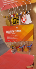 A collection of wine glass charms from Shrinky Chains, created by Arabella Camunez, are displayed at the Las Cruces Farmers and Crafts Market.