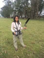 Grace Smith-Vidaurre holds equipment and large boom microphone to record parrot vocalizations during fieldwork in Uruguay.