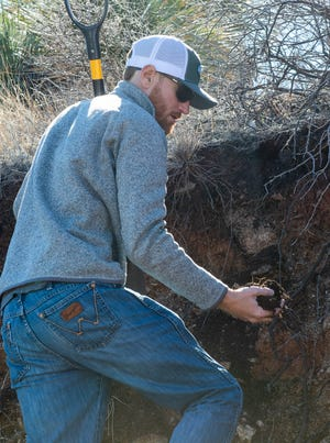 Jeremy Schallner, a Ph.D. student in the Department of Animal and Range Sciences, holds a handful of soil while visiting the Aguirre Spring Campground in February.