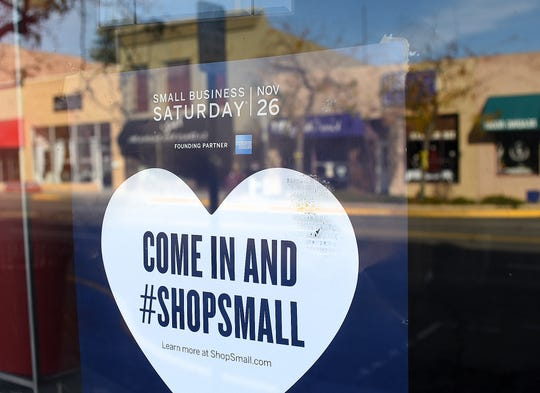 A poster advertising Small Business Saturday is taped on Nov. 24, 2016 in the window of the Chile Pod in downtown Farmington.