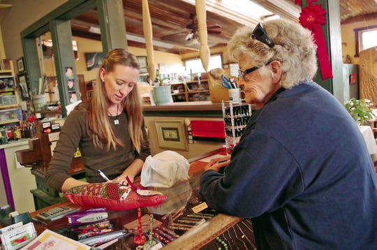 Tara Taylor, left, sells merchandise to a customer during Small Business Saturday on Nov. 30, 2013 at Artifacts Gallery in Farmington. Taylor's family owns the store in downtown Farmington.