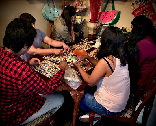 A Ventura County woman, who is slated to be deported June 11, plays lotería with her four children at their home. The Desert Sun is only using the woman's last name, Lopez, to protect her family's privacy.