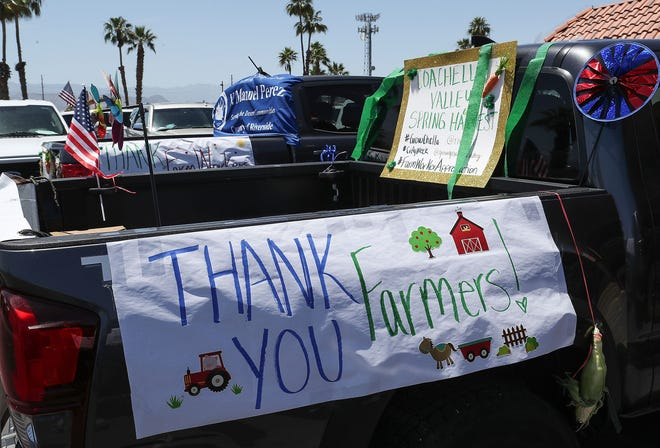A vehicle sports signs thanking those in the ag industry in the Coachella Valley Spring Harvest Farm to City Parade in Coachella, May 22, 2020.