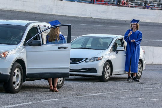 """Pensacola Private School of Liberal Arts graduating seniors Rayna Dyer, left, and Sean McMann play rock, paper, scissors from their cars before the start of their graduation ceremony at Five Flags Speedway on Friday. Instead of a traditional walk, students drove around the racetrack while """"Pomp and Circumstance"""" played."""