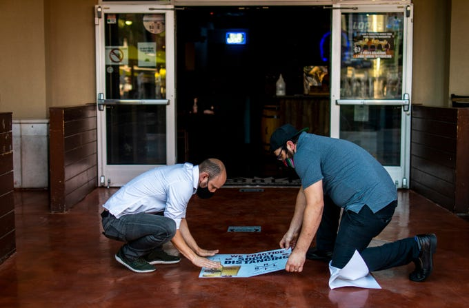 General Manager Jamie Seda (left) and Manager JP Dete set up a social distancing sign at Salt Tacos and Tequila at the Westgate Entertainment District on May 22, 2020.