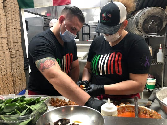 """Divino Pizzeria & Grille owner Jason Eckenrode (left) and his sister Samantha (right) prepare ingredients for the """"Mona Lisa"""" pizza, a $400 specialty pie."""