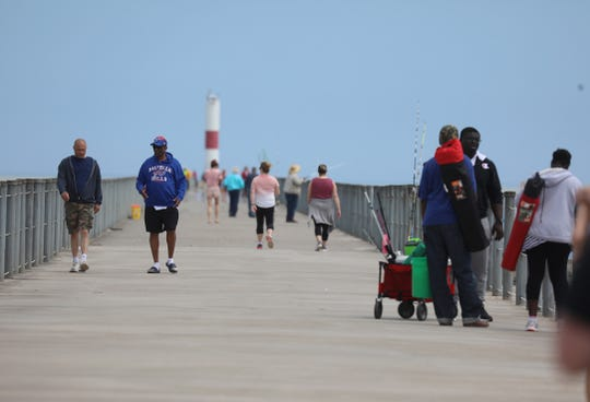 With the nicer weather, many people head down to Ontario Beach and walk along Charlotte Pier Saturday, May 23, 2020.