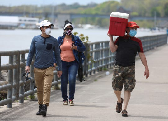 Luis Lopez heads out to a spot on Charlotte Pier with his son, Luis Lopez Jr. and wife, Muriam Miranda, Saturday, May 23, 2020.