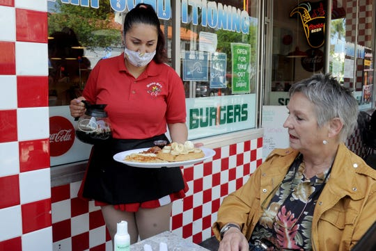 Nancy Vargas serves breakfast to Connie Miller of Lancaster at Busy Bee Cafe in Ventura on Saturday, May 23, 2020. Ventura County was approved to expand to Phase 2 of reopening just before Memorial Day weekend.