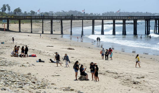 People hang out by the Ventura Pier on Saturday, May 23, 2020.