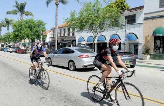 People bike along Main Street in Ventura on May 23, 2020. Ventura County was allowed to advance to the second stage of reopening just before Memorial Day weekend.