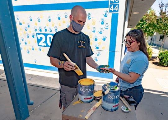 Exeter teacher Jason Welch, left,  paints senior Melissa Lara's hand on Friday, May 22, 2020. Painted hand prints were one of the few remaining traditions that Exeter High School seniors were allowed to continue after concerns about COVID-19 shut down campuses nationwide.