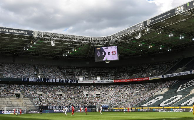"A banner reading ""For Borussia, against ghost matches"" is displayed during the German Bundesliga soccer match between Borussia Moenchengladbach and Bayer Leverkusen, in Moenchengladbach, Germany, on May 23, 2020. Leverkusen won the match, 3-1."