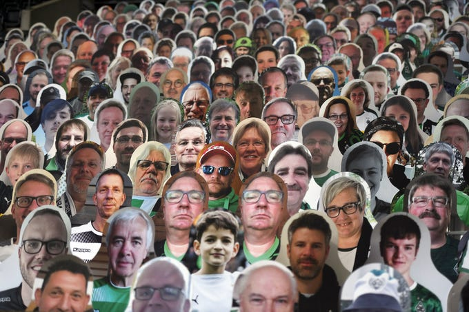 Cardboard pictures of fans are placed in the stands prior to the German Bundesliga soccer match between Borussia Moenchengladbach and Leverkusen, in Moenchengladbach, Germany, Saturday, May 23, 2020.