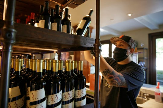 Jesse Cierly stocks a tasting bar shelf with bottles of wine at the Francis Ford Coppola Winery in Geyserville, Calif. The winery has been closed the past two months because of the coronavirus threat and is preparing to reopen to visitors.