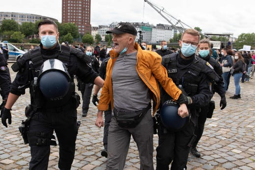 A protester is taken away by police officers during a rally against restrictions in place to limit the spread of the new coronavirus COVID-19 pandemic on May 23, 2020 in Frankfurt am Main, western Germany.