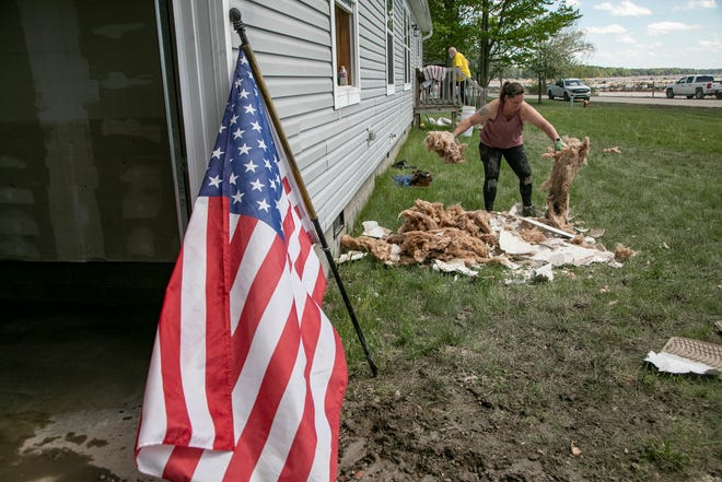 Katie Spencer, 41, of Lapeer volunteers Sunday at the house of Donald Martin whose Sanford Lake home was severely damaged by floodwaters. Floodwaters have devastated communities like Midland and Sanford following the failure of two dams along the Tittabawassee River.