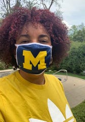 Lorraine Wangler models a sample of the University of Michigan masks that should be available at the M Den by the end of this week.