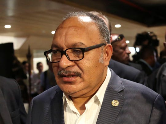 FILE - In this Nov. 18, 2018, file photo, Papua New Guinea's Prime Minister Peter O'Neill is chased by reporters after reading his statement at the end of the APEC 2018 summit at Port Moresby, Papua New Guinea.