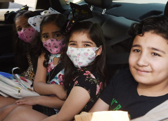 Adam Aljabiri, 8, of Dearborn Heights, right, and his sisters Layla, 6, Nora, 6, and Jennah, 7, wait for their bags of candy during the drive-thru Eid al-Fitr celebration to mark the end of the Ramadan fasting month at Islamic Center of America in Dearborn.