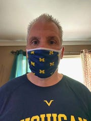 Former Michigan football player Vincent DeFelice (1980-84) models a sample of the University of Michigan masks .