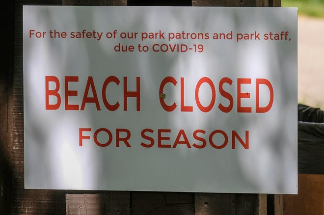 A sign at the entrance to Burchfield Park in Holt indicates the beach will be closed for the season Sunday, May 24, 2020.