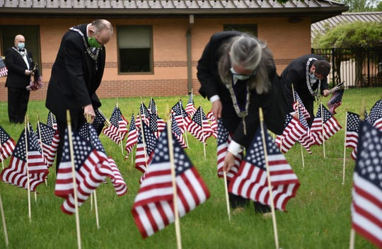 Members of the Passaic Valley Elks Lodge, including veteran Bob Keller, second from left, honor each of the over one hundred veterans who have passed away from Covid-19 at the New Jersey Veterans Home in Paramus by placing one flag for each veteran on the front lawn of the home on May 24, 2020.