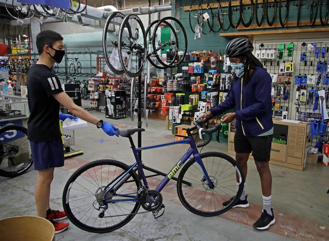 Joel Johnson, right, takes delivery of his new bicycle Friday, May 15, 2020, at the Sports Basement store in San Francisco.