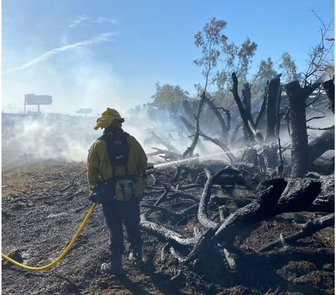 A Cal Fire firefighter hoses down hot spots during a vegetation fire at Avenue 42 and Country Club Drive Sunday, May 24, 2020. The fire charred an acre.