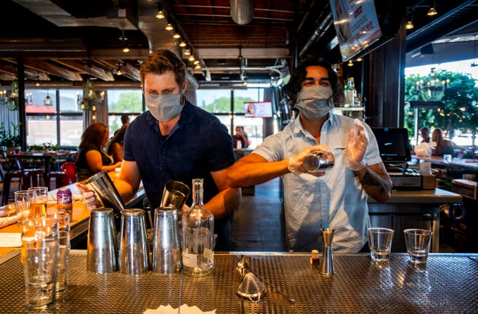 Bartenders Chase Watts, right, and Luke Valenzuela make drinks at Culinary Dropout in Phoenix on May 22, 2020.