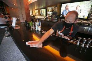 Greg Neises, a bartender, wipes down the bar after serving a guest at the Hotel Valley Ho in Scottsdale on May 22, 2020.