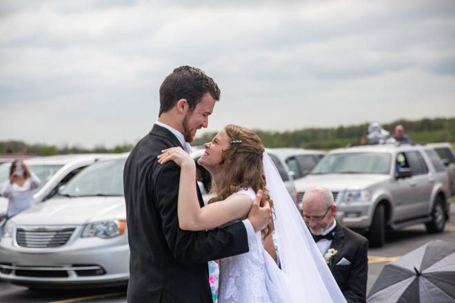 Kaitlyn Steele and Joshua Latham dance at their drive-in wedding ceremony at Ross Bible Church in Port Huron Township on May 23, 2020.