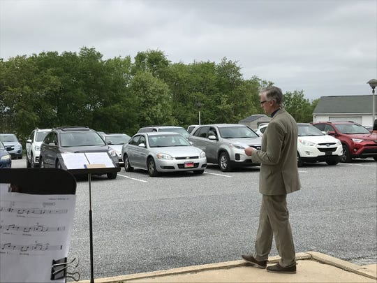Tab Cosgrove, pastor at St. John Lutheran Church in Springettsbury Township, leads the church's first drive-in service on Sunday. The pastor is planning another next Sunday.
