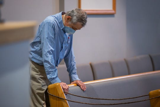 A man bows his head in prayer as he attends a reopened Sunday service at Calvary Bible Church, Sunday, May 24 in Hanover, PA. The church reopened for Sunday services on May 17, implementing several measures to maintain social distancing, such as closing off every other pew, seating attendees by household, and encouraging masks. The service was also livestreamed for those who chose to not attend.