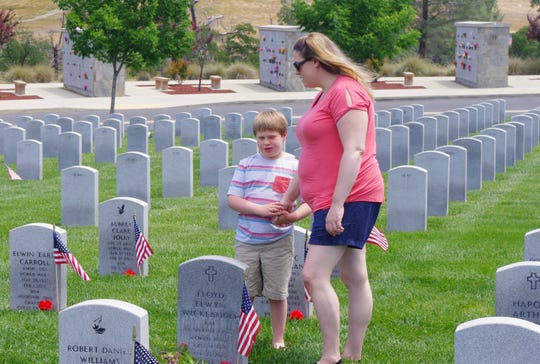 Stephanie Kvale and her son Graeme, 7, on Sunday visit the grave of Kvale's great grandfather Floyd Elwyn Wicklander, a World War II veteran, at the Northern California Veterans Cemetery in Igo.