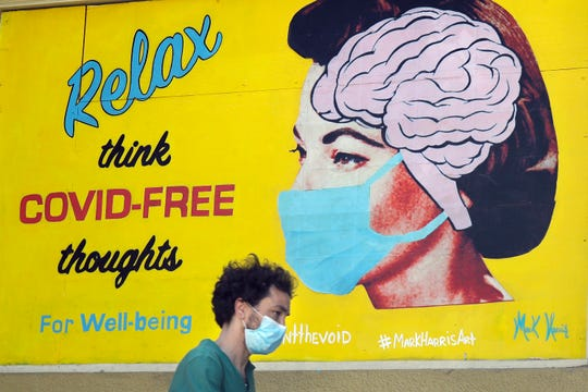 """A man wears a face mask while walking under a sign that reads """"Relax think COVID free thoughts"""" during the coronavirus outbreak in San Francisco, Saturday, May 23, 2020. (AP Photo/Jeff Chiu)"""