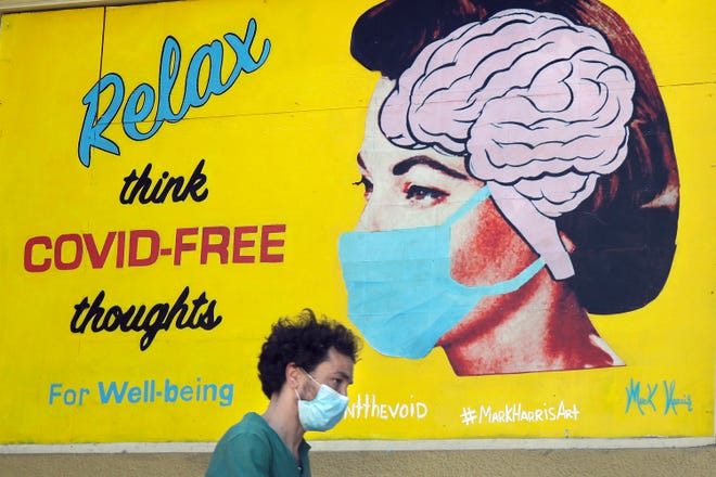 "A man wears a face mask while walking under a sign that reads ""Relax think COVID free thoughts"" during the coronavirus outbreak in San Francisco, Saturday, May 23, 2020. (AP Photo/Jeff Chiu)"