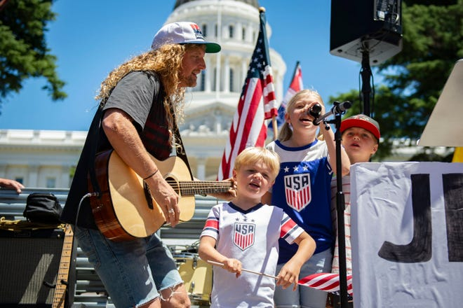 "Sean Feucht sings on stage with his family, Ezra, 5, Keturah, 9, and Malachi, 7, in front of the west steps of the state Capitol as protesters gathered at Liberty Fest to protest Gov. Gavin Newsom's stay-at-home order in Sacramento, Calif., on May 23. Feucht, an evangelical musician and activist, is planning three stops in Wisconsin this week as part of his ""Let Us Worship"" tour"