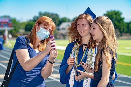 Rebekah Foster holds the phone with her daughters Bella Foster and Kaylee Foster for a video call with family across the U.S. on Saturday, May 23, 2020. Exeter High School graduates took their turn one-by-one on a small stage, seen by groups of family and friends, to be acknowledged and video recorded. A combined video and still pictures will be available later. Social distancing spread the ceremony from morning to afternoon with specific time blocks based on the alphabet. Both girls graduated Saturday, Bella from the high school and Kaylee from Wilson Middle School.