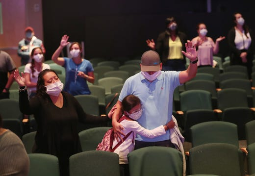 Margaret Cruz, Sophia Perez and Edwin Perez pray together after returning to Potential Church as it opened on May 24, 2020 in Cooper City, Fla. The church reopened it's doors to a select group of people with safety measures in place after hearing President Donald Trump announcing on Friday that governors around the country should allow houses of worship to reopen.