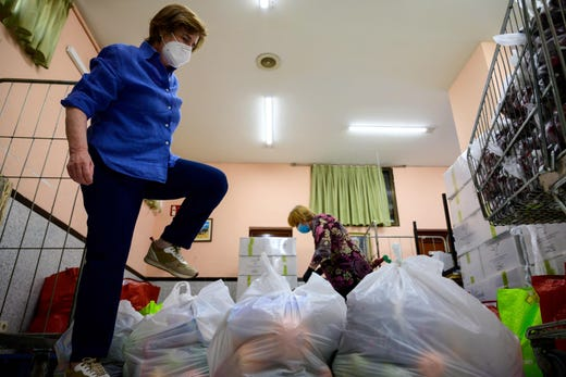 Ana and a fellow volunteer prepare food rations to be distributed to people in need at the Nazaret Association food bank in Madrid on May 24, 2020. The association who is attending to 600 people warned that due to the economic crisis caused by the novel coronavirus outbreak many people have barely any resources left.