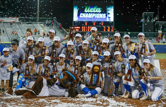 UCLA players pose for photos after defeating Oklahoma in the 2019 Women's College World Series in Oklahoma City.