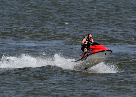 Choppy conditions Saturday briefly lift a rider and his personal watercraft out of the water at Lake Fort Phantom Hill.