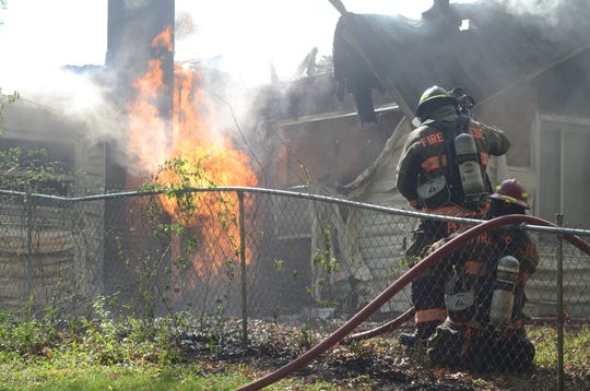 Firefighters watch as a broken natural gas line continues to burn at house fire in Pennfield Township on Sunday.  Trace Christenson/The Enquirer